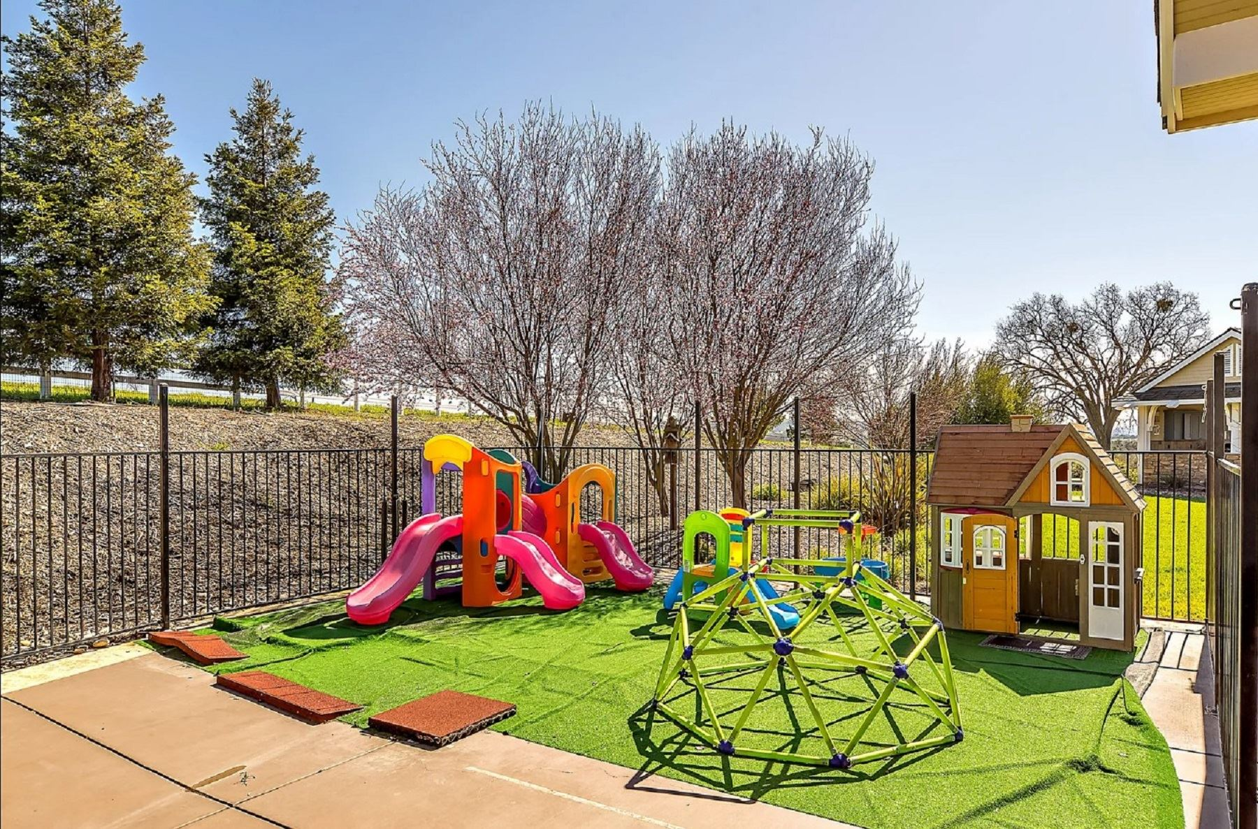 Frontier Farmhouse - Exterior - Playground in fenced in backyard with fake grass laid out