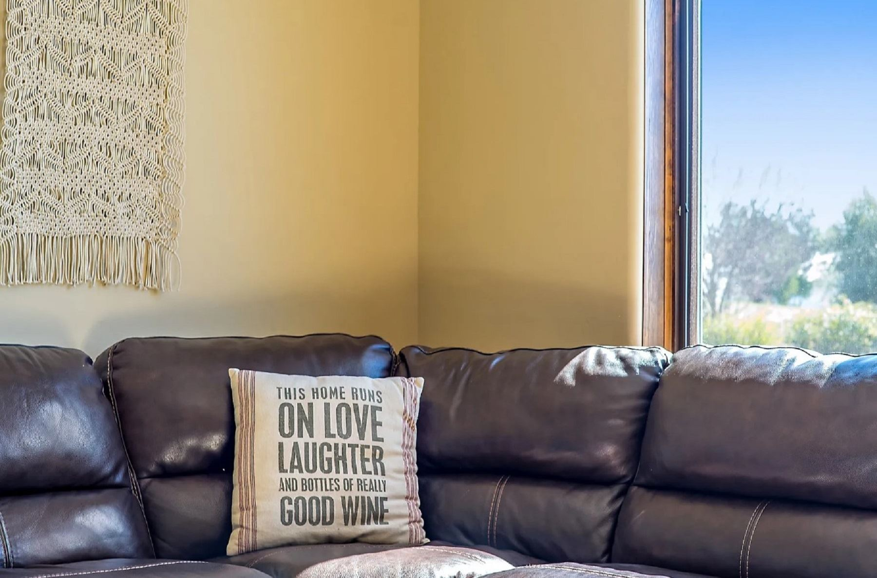 Frontier Farmhouse - Interior - Close up on corner of leather sectional and decor pillow that says This Home Runs on Love Laughter and Bottles of Really Good Wine