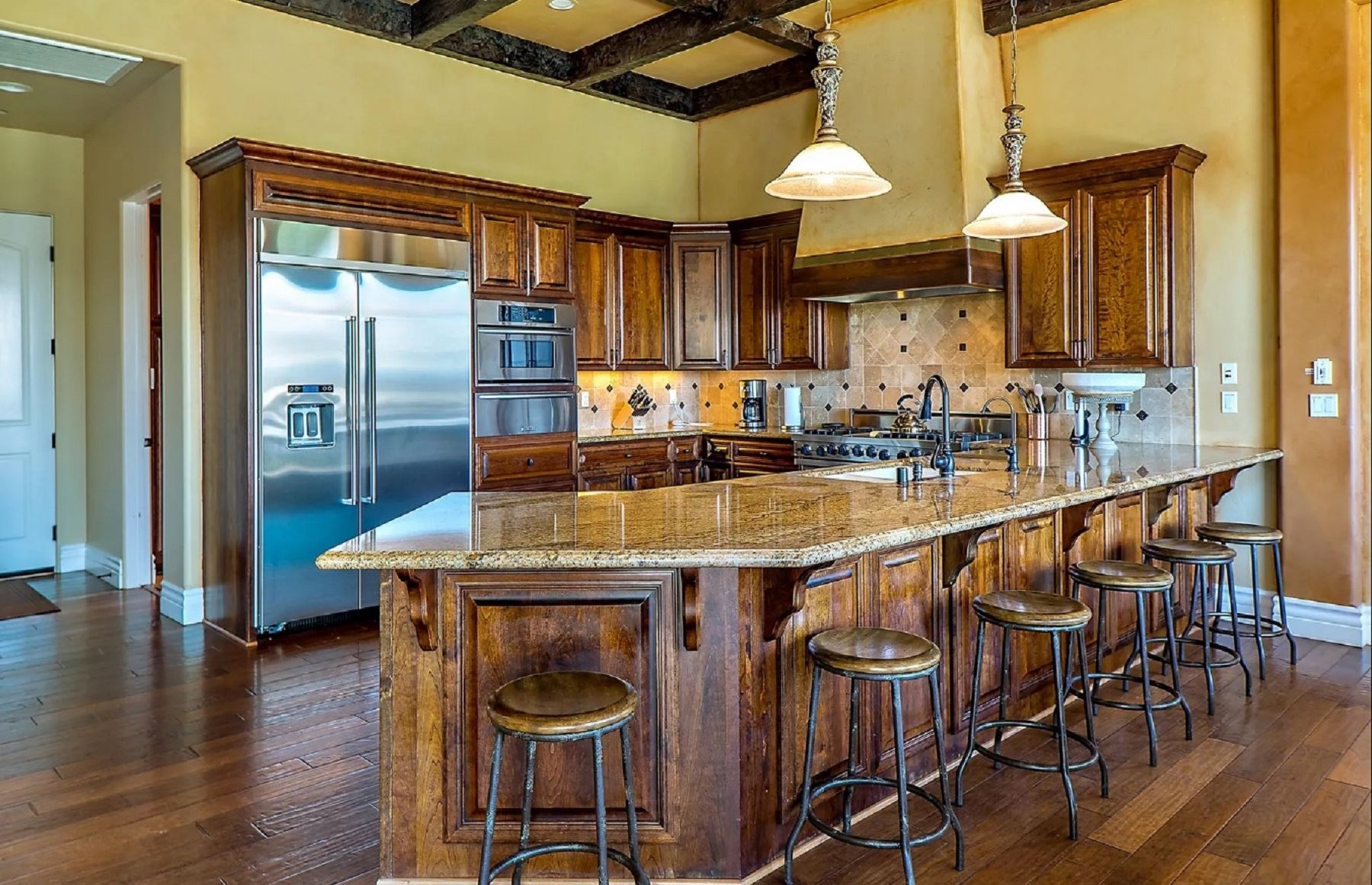 Frontier Farmhouse - Interior - Kitchen with wide island that has six barstools for eating at the breakfast bar