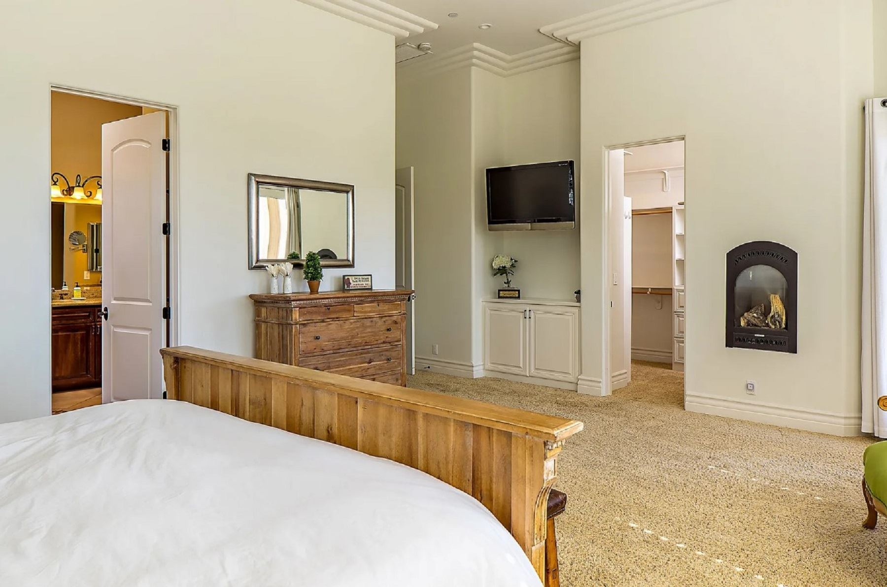Frontier Farmhouse - Interior - Large Bedroom with dresser and mirror as well as view into onsuite
