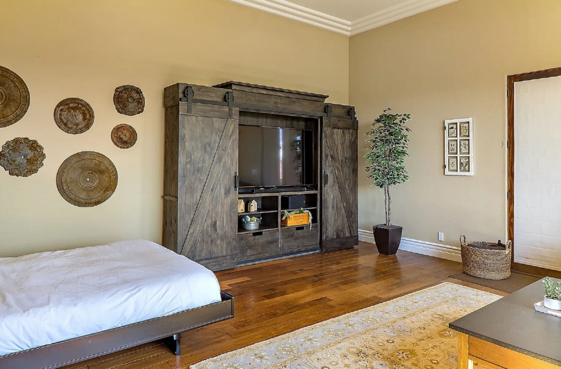 Frontier Farmhouse - Interior - Living area with murphy bed and TV console encased in bar doors