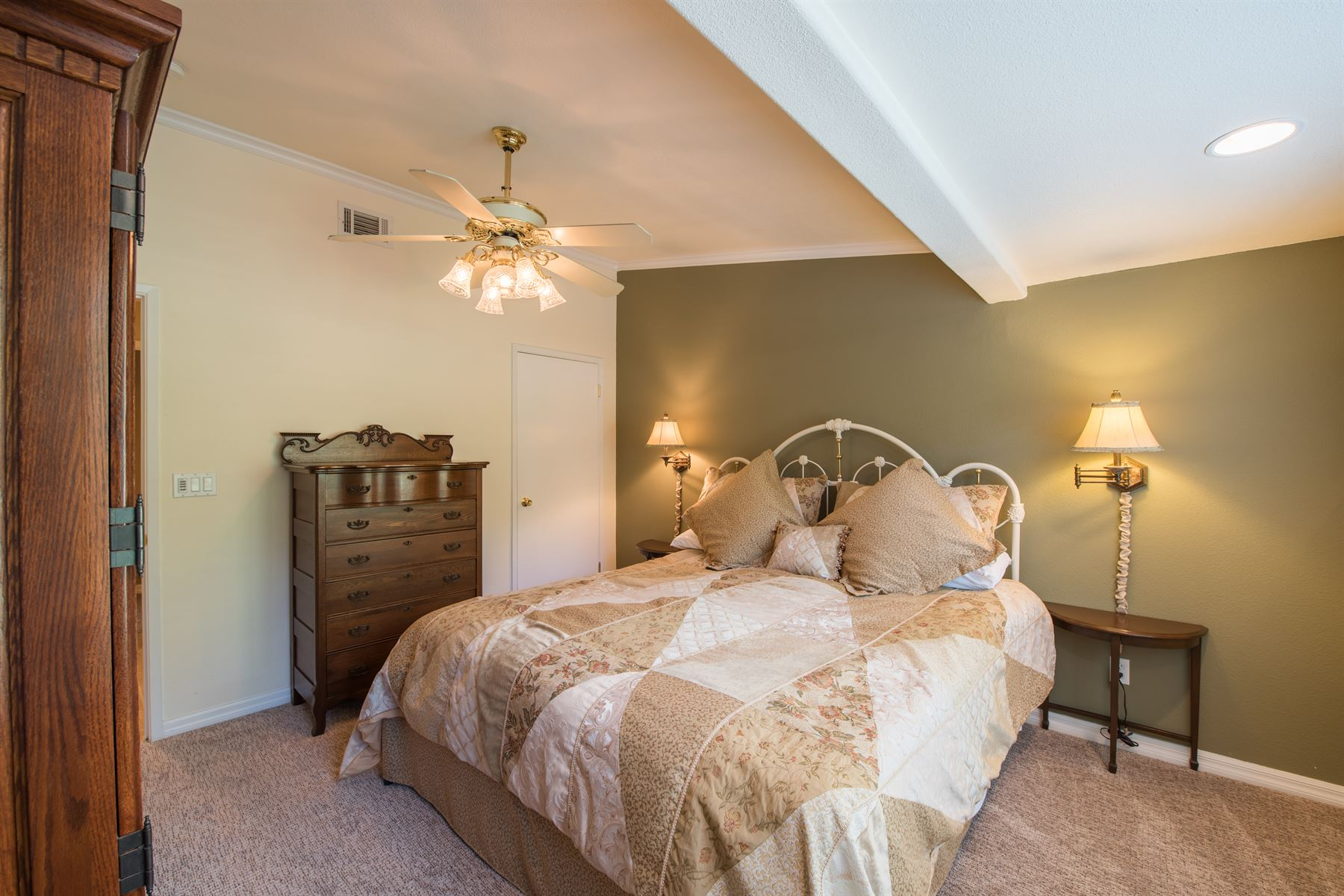 Golfer's Getaway - Interior - Bedroom with large bed that has tan and peach checkered linens and a ceiling fan