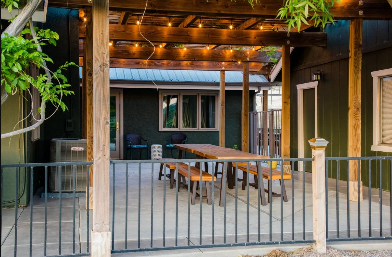 Harvest Ridge Ranch - Exterior - Picnic Dining Table under a pergola with tiny lights suspended within it
