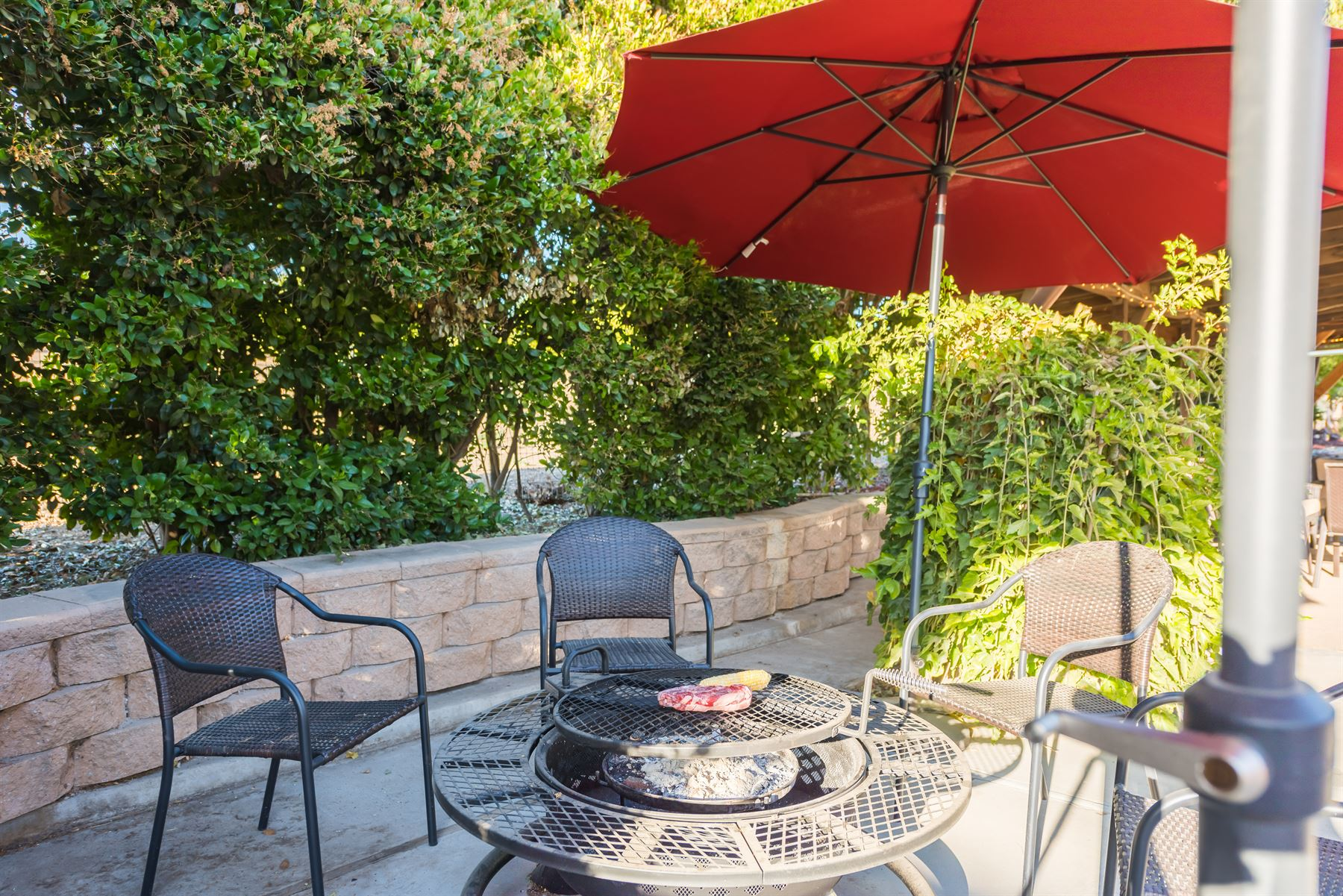 Oak Pass Ranch - Exterior - Circular grill and firepit with seating for four under an umbrella