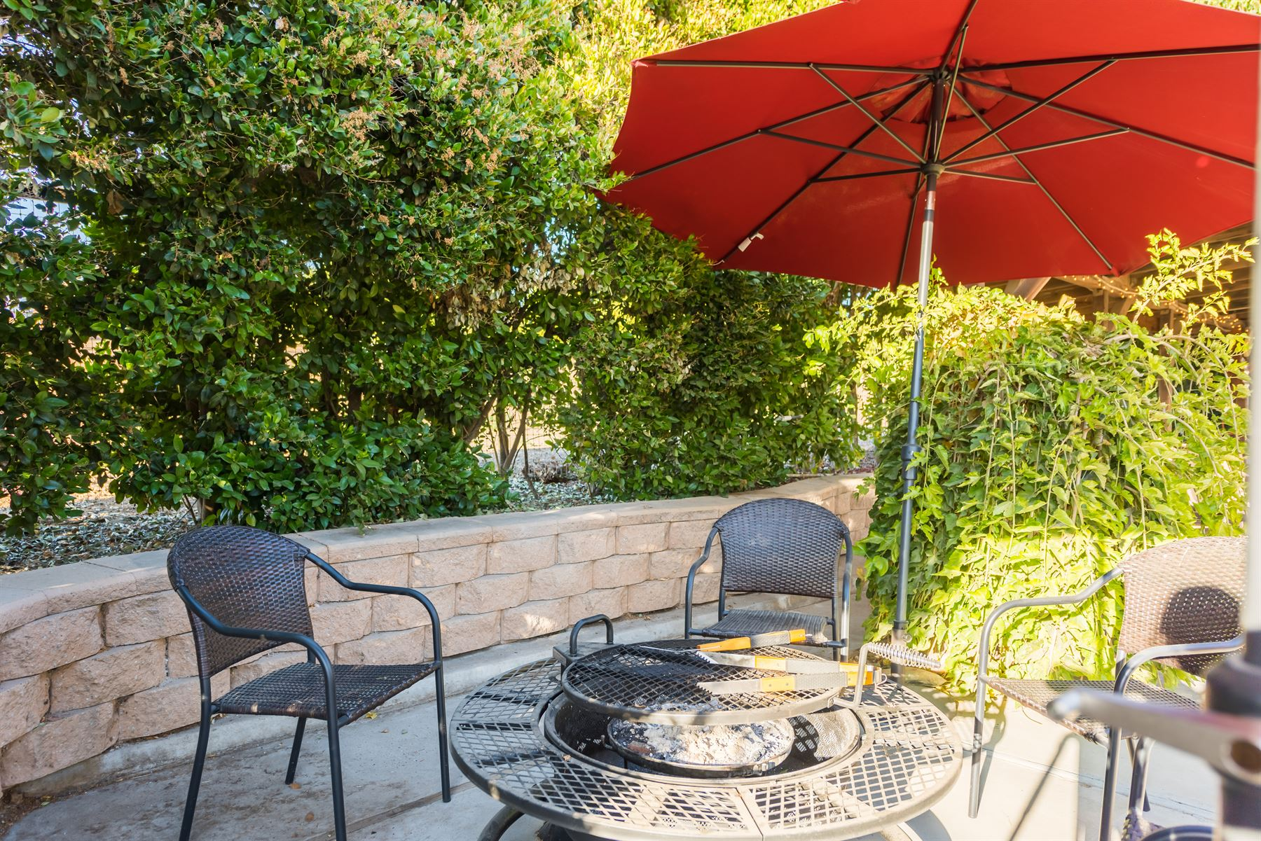 Oak Pass Ranch - Exterior - Circular grill with tongs that has seating for four under an umbrella
