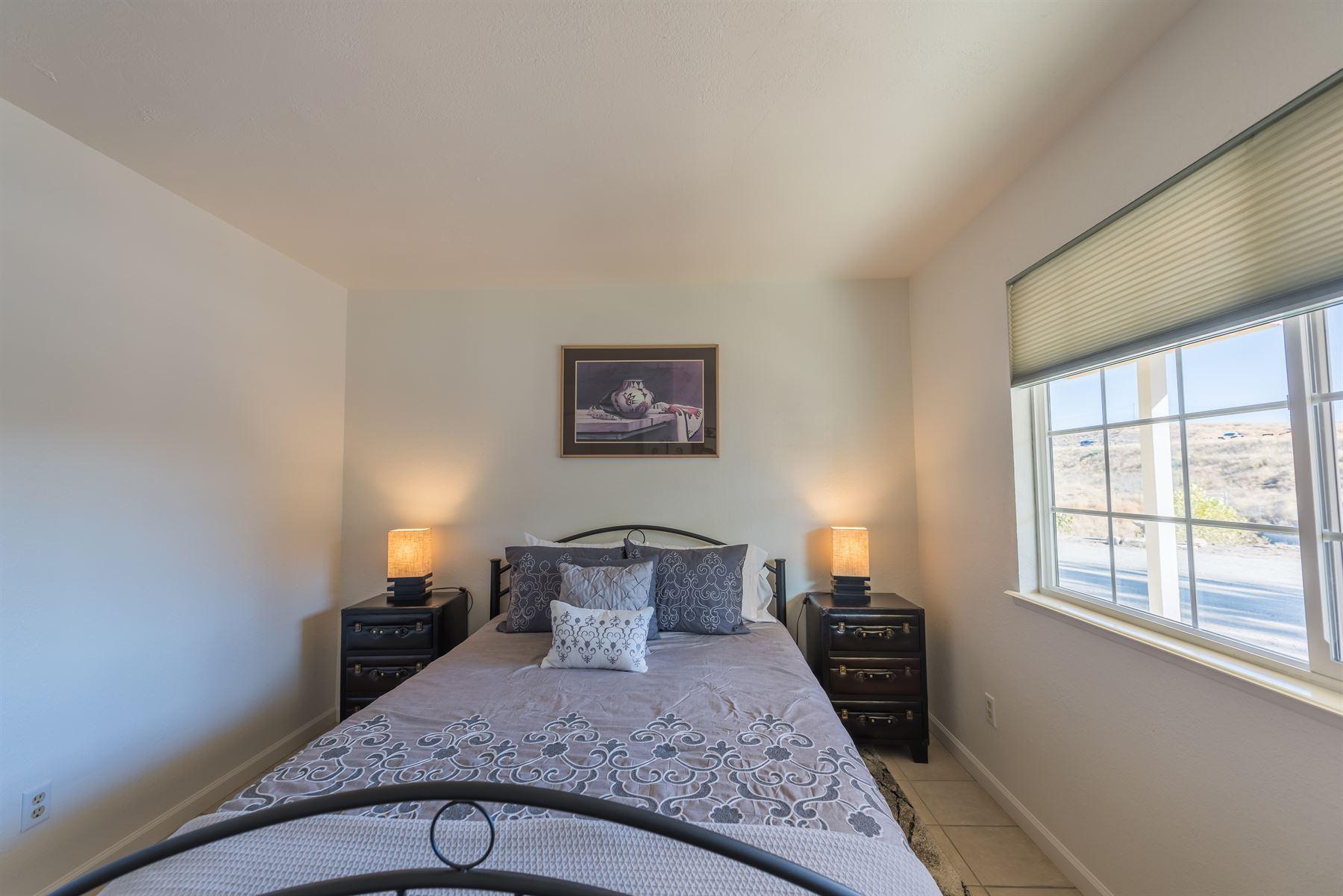 Oak Pass Ranch - Interior - Bedroom with grey linens - wide shot