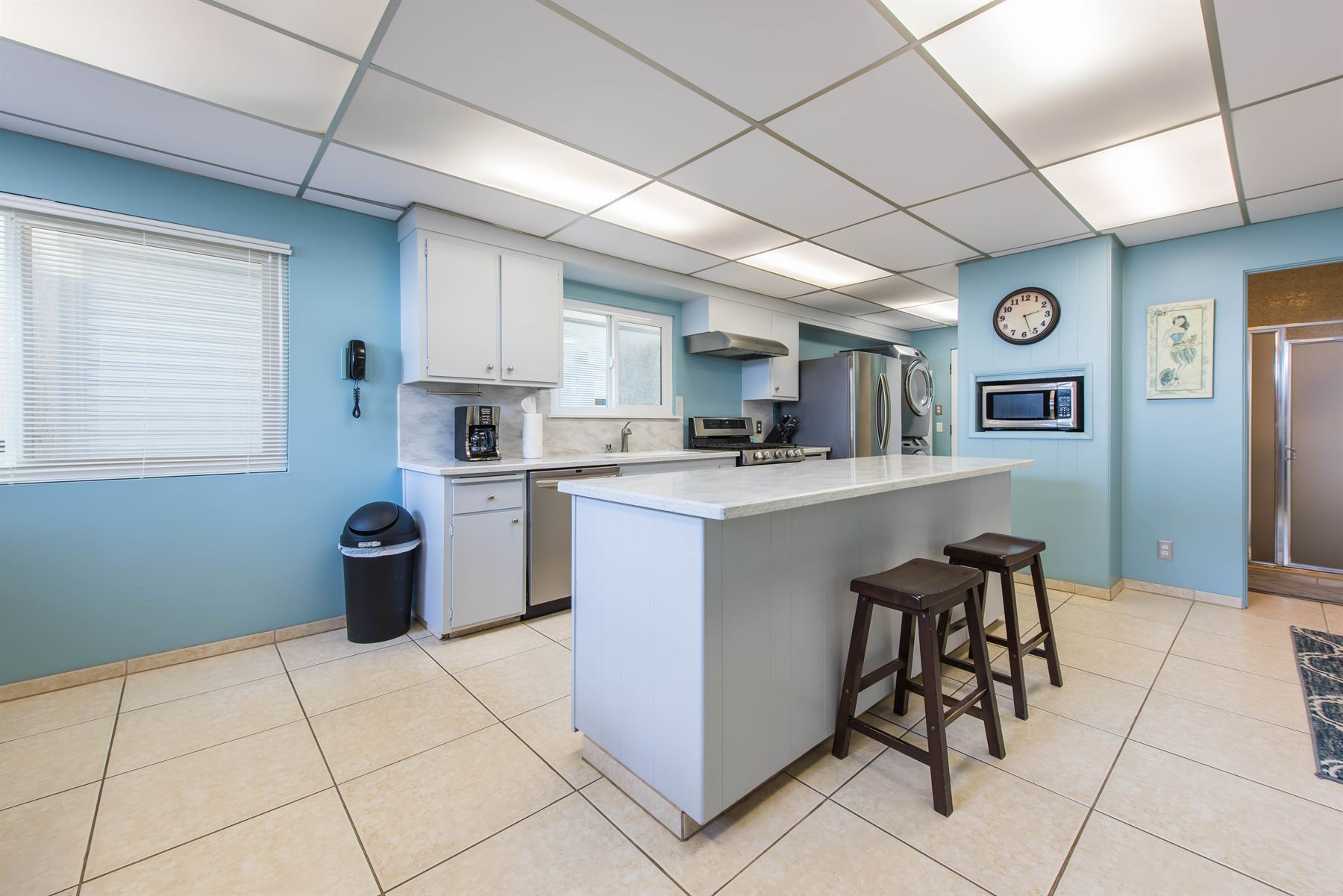 Oceanview Hideaway - Interior - Kitchen with light blue walls and island counter that has two barstools to sit at