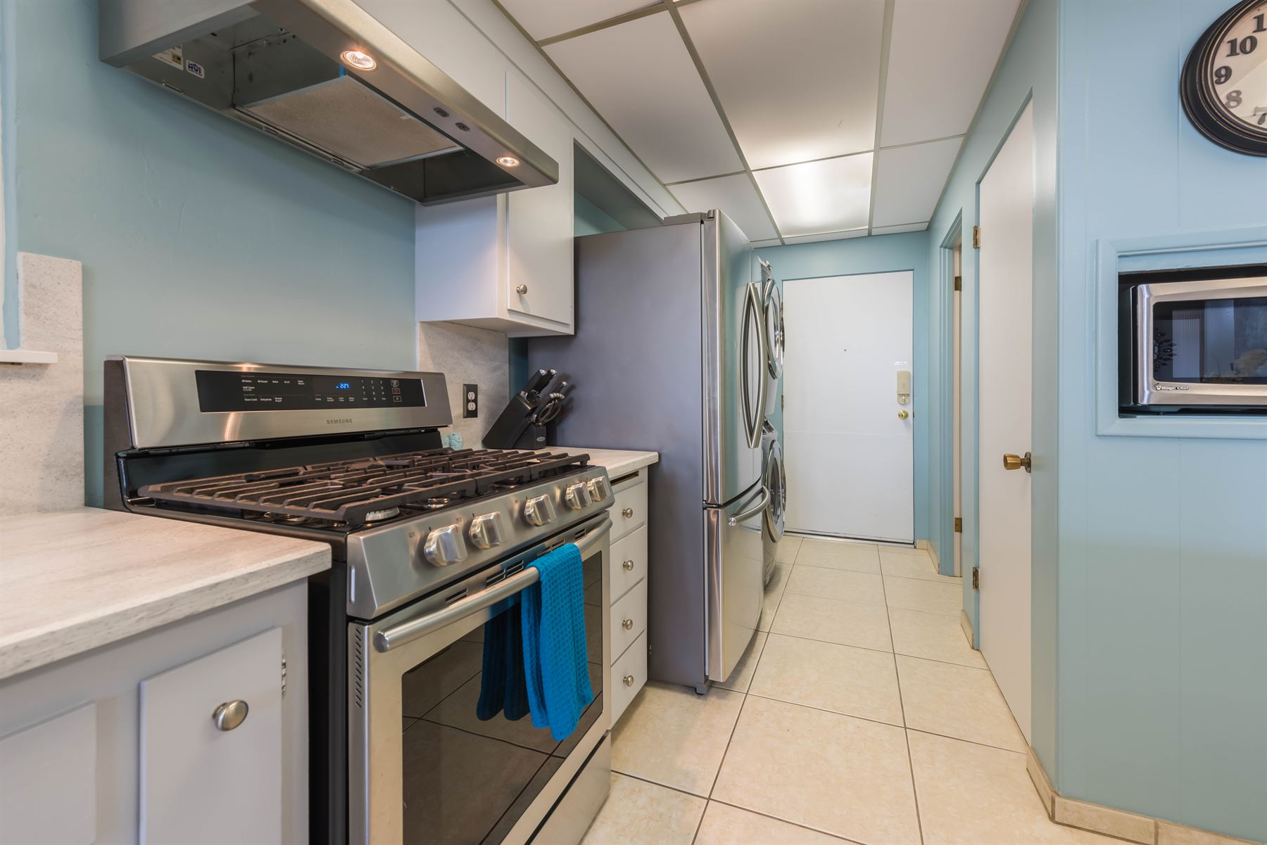 Oceanview Hideaway - Interior - Kitchen with view of stove and hallway that has the fridge and the stacked washer/dryer