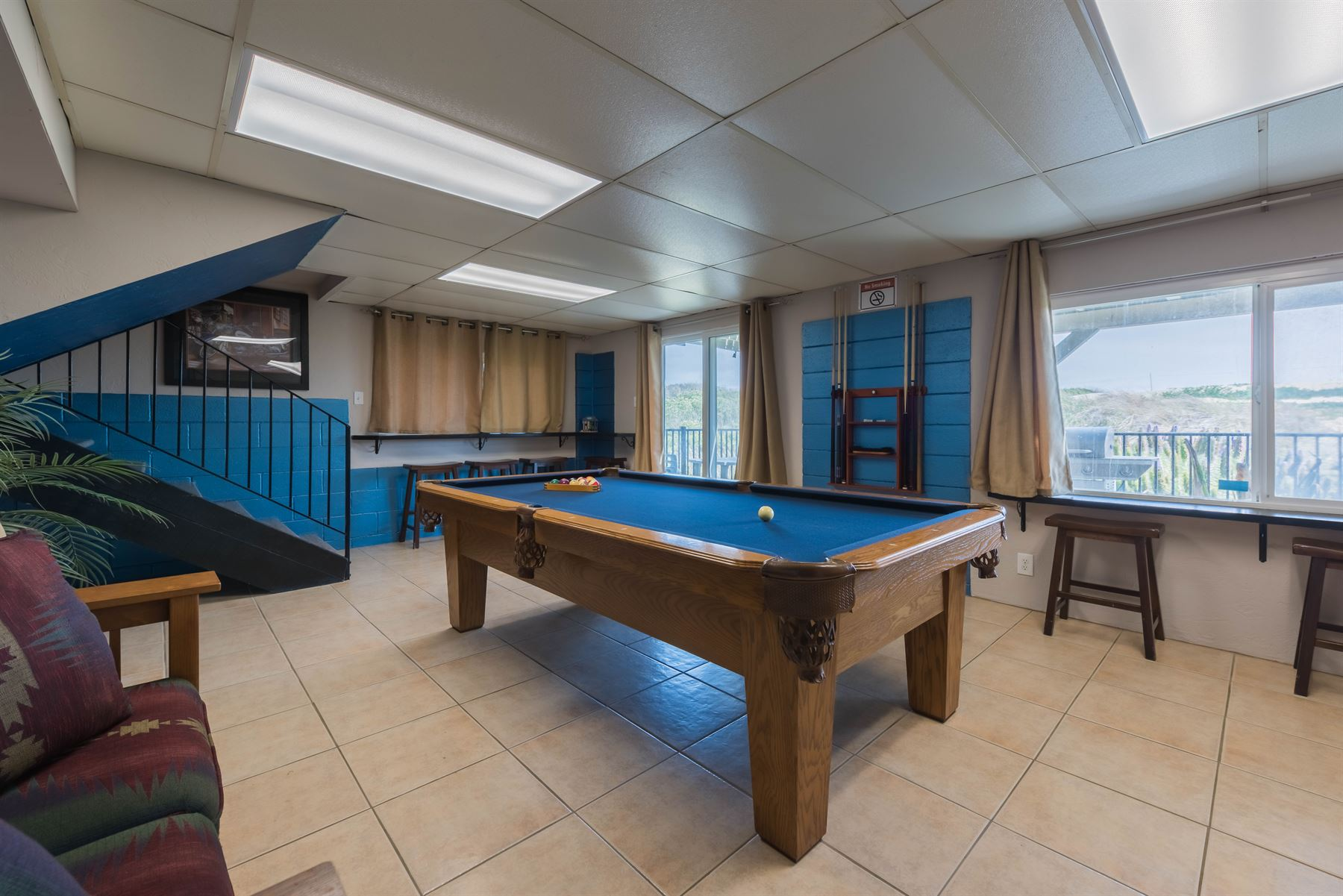Oceanview Hideaway - Interior - Game room with view of stairs going back up to main living space and view through windows and sliding glass doors to the porch with a grill and seating