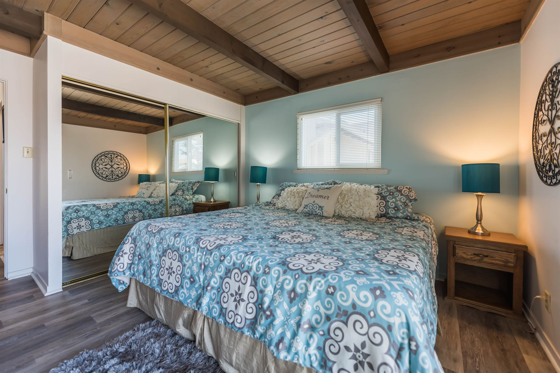 Oceanview Hideaway - Interior - Bedroom with queen bed and sliding mirrored doors to a closet