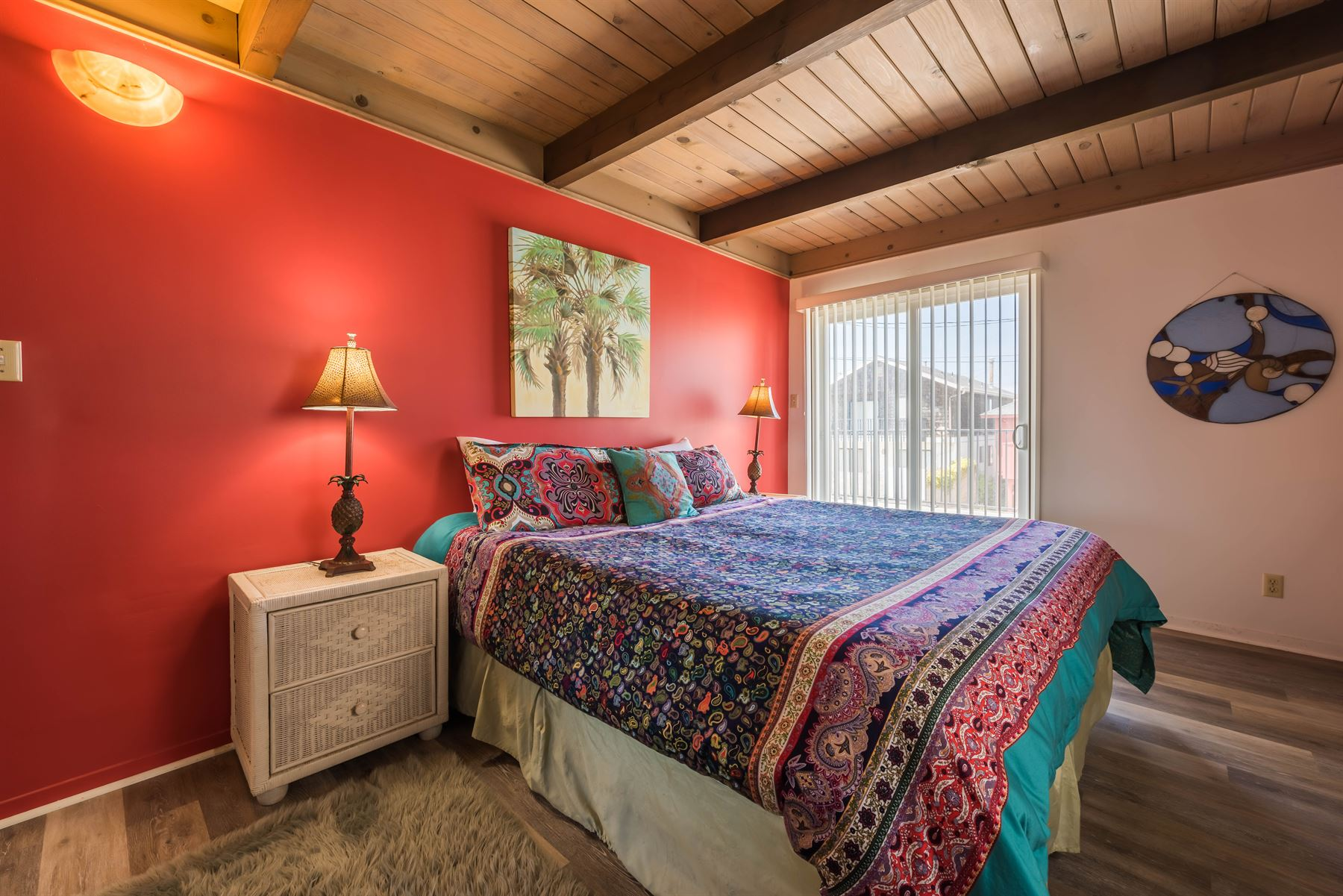 Oceanview Hideaway - Interior - Bedroom with red accent wall and wicker endtables beside a queen bed