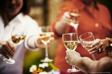 Women outdoors in park toasting with white wine glasses. Horizontal shot.