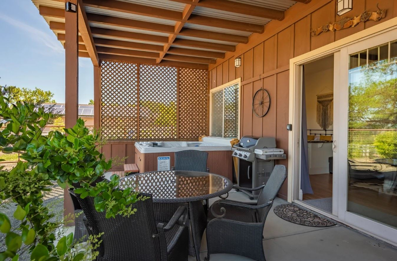Frontier Hideaway - Patio with hot tub and grill as well as circular table with seating for four