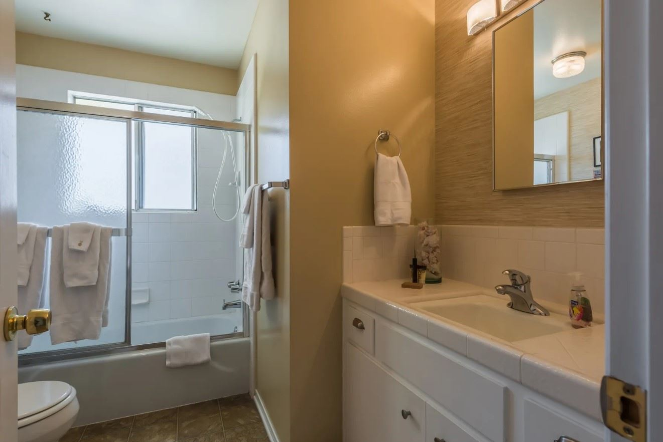 Morro Bay Rock Revival - Interior - Bathroom with short sink toilet and tub shower combo