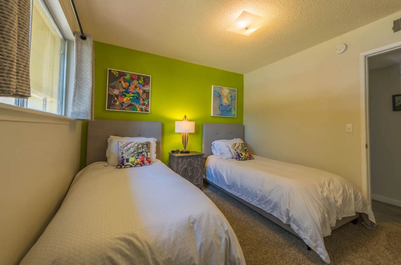 Morro Bay Rock Revival - Interior - Bedroom with two twin beds and lime green accent wall
