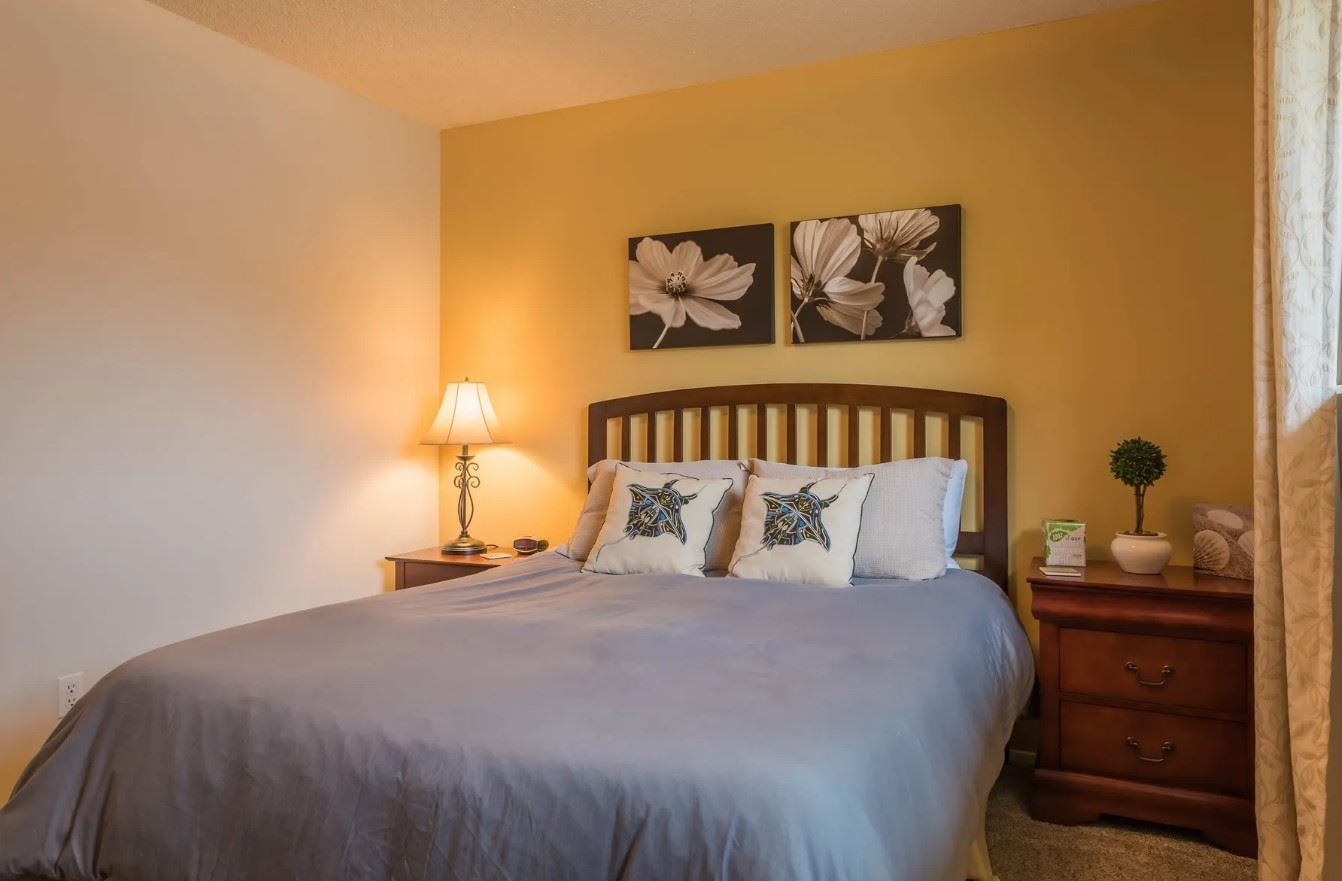 Morro Bay Rock Revival - Interior - Bedroom with yellow accent wall and blackwhite flower paintings