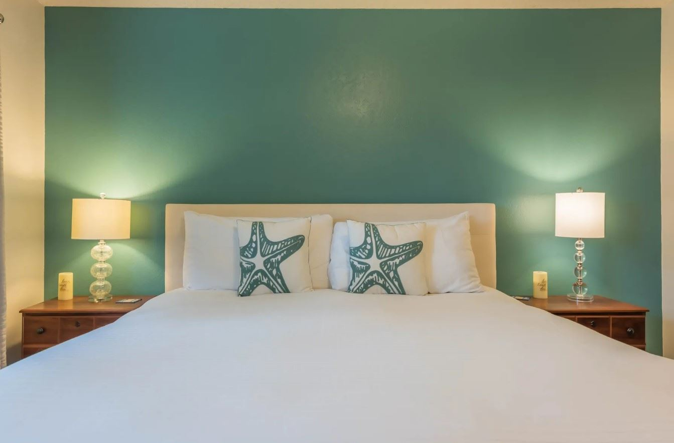Morro Bay Rock Revival - Interior - Close up shot of bed and endtables with green accent wall behind